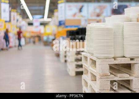 De nombreuses planches sur l'étagère du magasin blanc de la cuisson. Des étagères dans une variété de plaques blanches dans le magasin. Cuisine en porcelaine. Banque D'Images