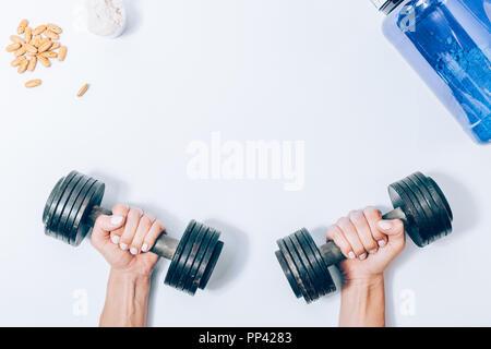 Télévision femme modèle mains tenant des haltères en métal à côté de la protéine en poudre et de vitamine comprimés, vue du dessus. Concept de l'amélioration de la force corporelle à l'aide de lourdes nous
