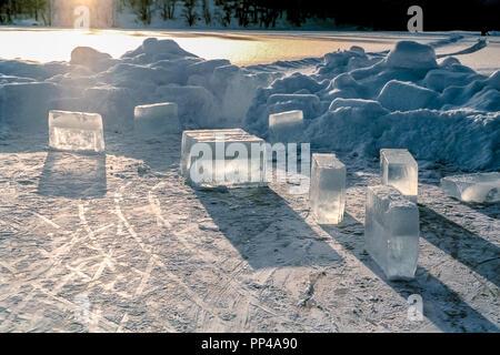 Gros cubes de glace sur un lac glacé avec de la neige et du soleil autour. Banque D'Images
