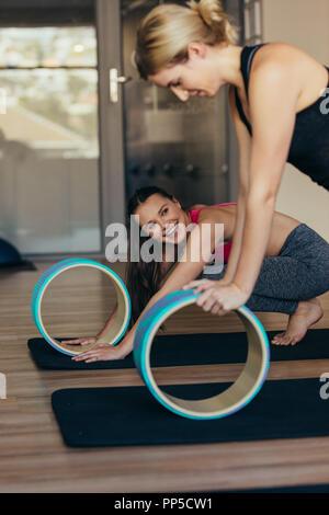 Femme de remise en forme à l'aide d'un entraînement pilates pilates yoga ou de roue. Femme de pousser jusqu'au repos position mains sur roue pilates. Banque D'Images