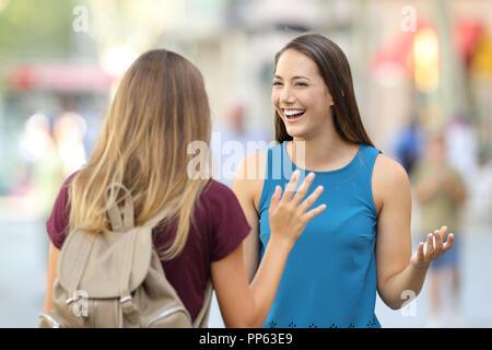 Deux amis heureux d'accueil et de réunion sur la rue avec un arrière-plan flou Banque D'Images