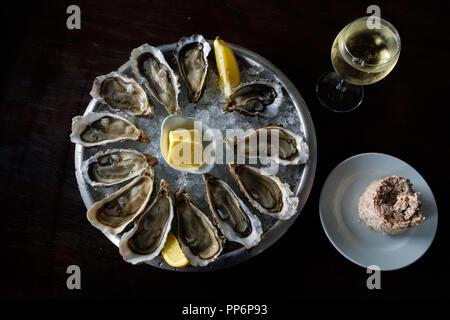 Une assiette d'huîtres du bassin d'Arcachon. Les huîtres sur un lit de glace au citron, beurre, un verre de vin et quelques pate Banque D'Images