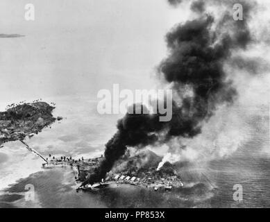 Guadalcanal-Tulagi les débarquements, 7-9 août 1942 - feux brûler entre les installations et les hydravions japonais sur l'île de Tanambogo, à l'est de Tulagi, sur le premier jour de l'invasion, 7 août 1942. Ce point de vue ressemble à propos de SSW, avec à gauche l'île de Gavutu, connecté à Tanambogo par une chaussée.