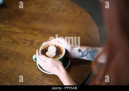 Une femme avec un tatouage bras est assis à une table en bois tenant une tasse de Cappuccino dans un bol vert