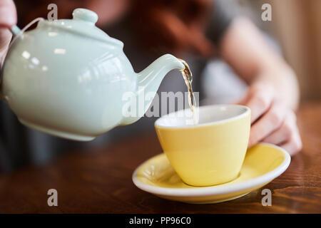 Red Head girl avec bras tatouage, assise seule dans un café se verse une tasse de thé comme elle s'assoit dans un café à Liverpool, Royaume-Uni