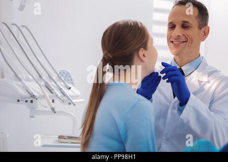 Sourire dentiste positive pendant le contrôle des dents de son patient Banque D'Images