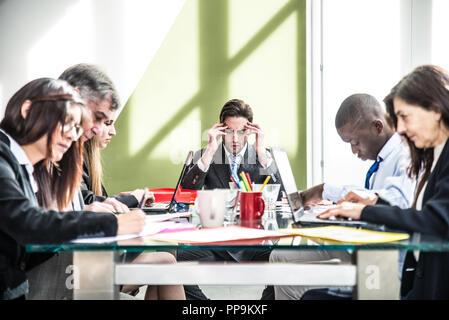 Businessman having maux de tête lors d'une rencontre d'affaires - personne dépressive avec des problèmes financiers Banque D'Images