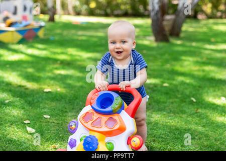 Cute little boy l'apprentissage de la marche avec walker toy sur l'herbe verte pelouse à l'arrière-cour. Bébé rire et s'amuser en première étape au parc sur journée ensoleillée à l'extérieur. Enfance heureuse concept Banque D'Images