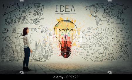 Vue latérale d'une pensive young woman looking at the wall avec ampoule colorée et des croquis. Unicité de l'idée et concept genius. Banque D'Images