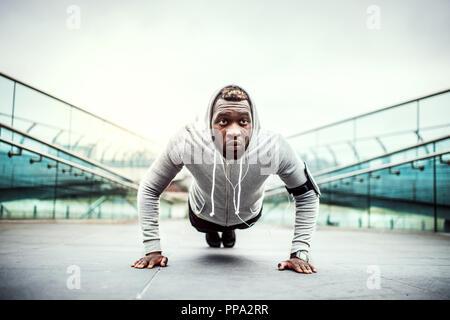 Young black man runner faisant push-ups sur le pont à l'extérieur dans une ville. Banque D'Images
