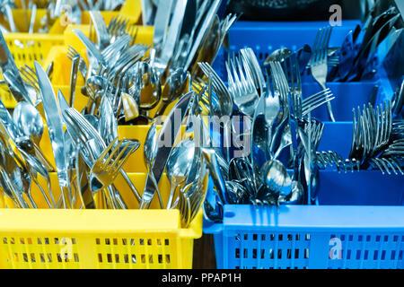 L'argenterie et coutellerie en ocntainer palstic colorés dans un restaurant industrielle cuisine propre et frais hors du lave-vaisselle Banque D'Images