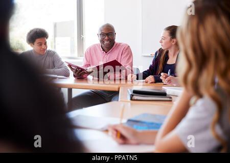 Lycée pour les garçons assis avec des étudiants à Tutor 24 en classe