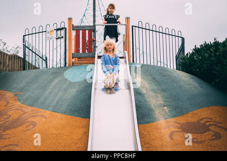 Fille blonde jouer sur diapositive dans play park Banque D'Images