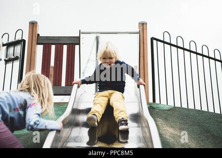 Petit garçon sur diapositive dans play park Banque D'Images