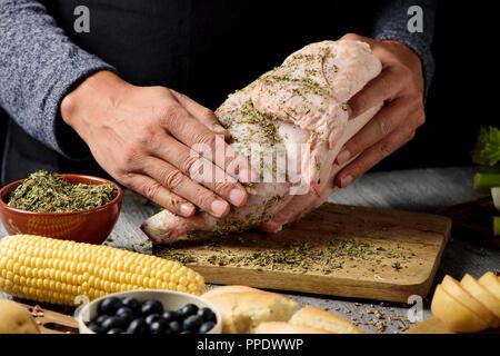 Libre d'un jeune homme de race blanche la préparation d'une Turquie placé sur une table rustique en bois plein d'ingrédients pour la farcir comme la pomme de terre, céleri, blueberrie Banque D'Images