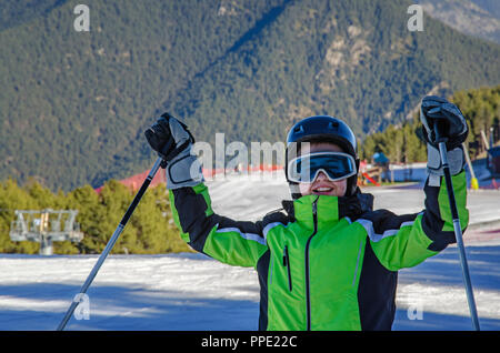 Heureux homme adolescent portant des vêtements de sport, casque et lunettes détient ses mains avec des bâtons de ski. Une infrastructure de ski et mo Banque D'Images