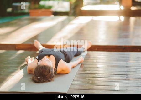 Jeune femme méconnaissable fait à l'extérieur, faisant du yoga l'exercice sur tapis gris, couché dans la posture de Shavasana - Corps Mort, se reposant après la pratique, meditati