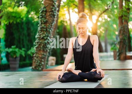 Concentrés girl sitting in lotus pose et de méditer ou de prier. Young woman practicing yoga seul sur une terrasse en bois dans la région de tropical island