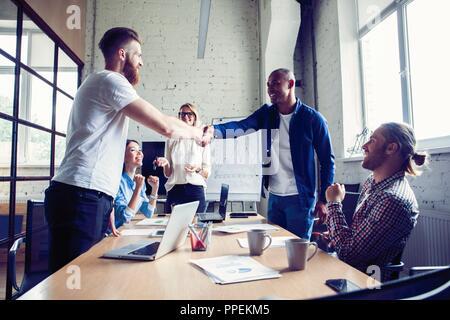 De nouveaux partenaires commerciaux. Les jeunes collègues moderne dans smart casual wear shaking hands and smiling while sitting in the creative office. Banque D'Images