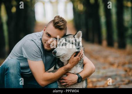 Young smiling man hugging dog husky in park Banque D'Images