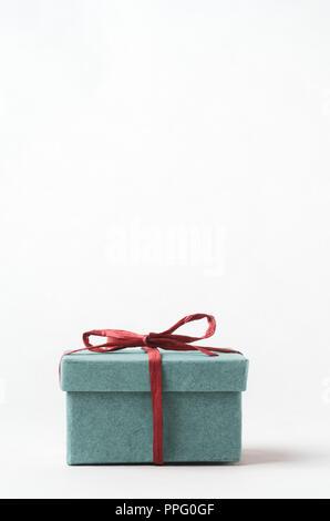 Un simple, clair, turquoise boîte-cadeau avec couvercle. Fermées et attachées avec un ruban de raphia rouge. Espace copie ci-dessus. Banque D'Images