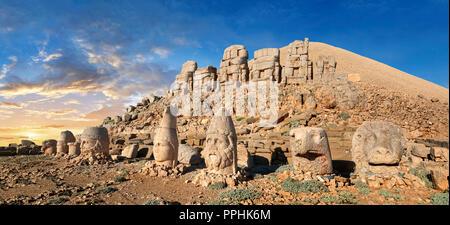 Statue tête au coucher du soleil avec des statues sans tête assis en face de la pyramide en pierre 62 AV tombe royale, terrasse est, le Mont Nemrut Dagi Nemrud ou Banque D'Images