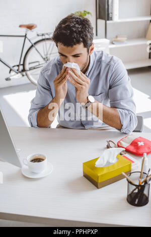 Sick woman blowing nose in tissue in office