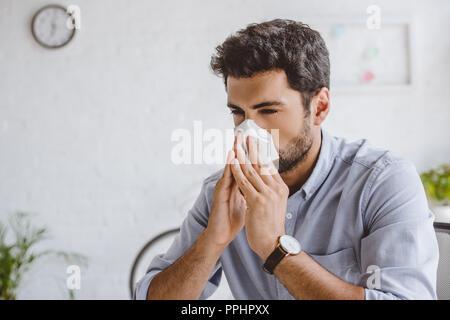 Gestionnaire malade nez soufflant dans les tissus dans office