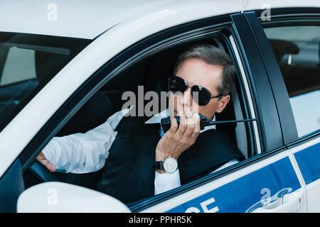 Les hommes d'âge moyen policier dans les lunettes de parler sur radio set in car Banque D'Images