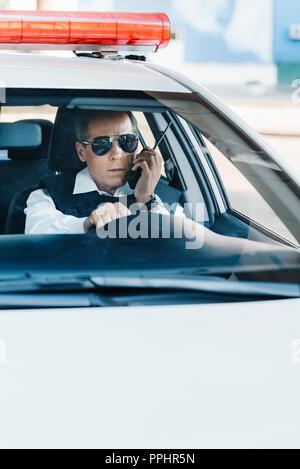 Policier d'âge moyen en parlant de lunettes sur radio set in car Banque D'Images