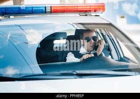 Âge moyen sérieux policier dans les lunettes de parler sur radio set in car Banque D'Images
