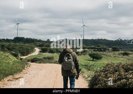 Un photographe ou vidéaste ou voyageur avec un sac à dos et le trépied à la main sur la route pour le Portugal et choisissez une belle vue pour prendre des photos ou enregistrer des vidéos. Banque D'Images