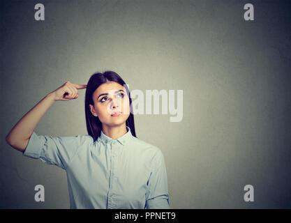Jeune femme brune perplexe se gratter la tête dans perplexion looking away Banque D'Images