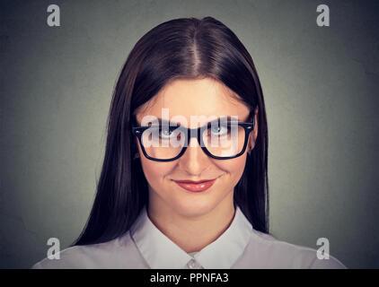 Jeune brunette timide en shirt et lunettes à la recherche jusqu'à la timidité sur fond gris Banque D'Images