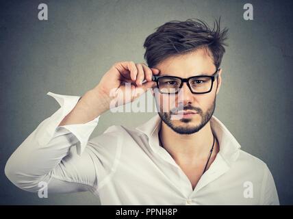 Portrait d'un bel homme à lunettes trendy looking at camera avec confiance sur fond gris Banque D'Images