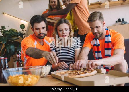Groupe d'amis en tenant les tranches de pizza fort sur la table à la maison Banque D'Images