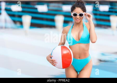 Girl in sunglasses holding inflatable ballon de plage au bord de la piscine Banque D'Images