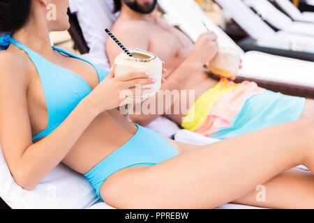 Portrait de couple sur les chaises longues avec des cocktails à la noix de coco Banque D'Images
