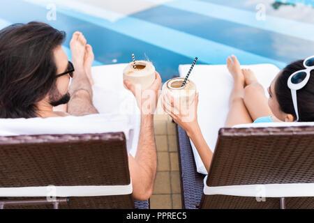 Vue de dessus de couple sur les lits de bronzage et de trinquer avec des cocktails à la noix de coco Banque D'Images