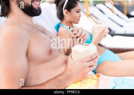 Couple avec des cocktails à la noix de coco sur les chaises longues, selective focus Banque D'Images
