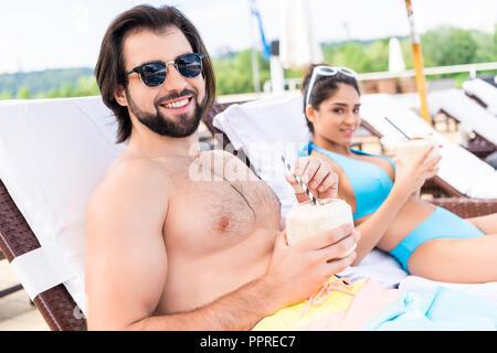 Jeune couple de détente sur les chaises longues avec lunettes cocktails coco Banque D'Images