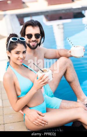Jeune couple à lunettes avec des cocktails à la noix de coco de détente à la piscine Banque D'Images