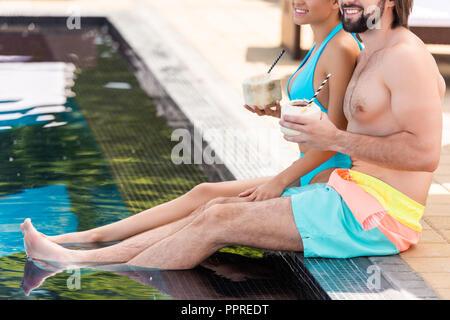 Portrait de couple se reposer près de la piscine avec des cocktails à la noix de coco Banque D'Images