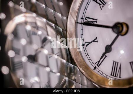 Close up arty shot d'une grande montre de poche en métal réveil à côté d'une boule disco argent Banque D'Images
