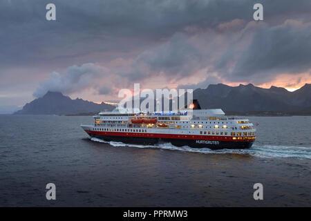 Le ferry Hurtigruten, MS FINNMARKEN, en direction du sud depuis Svolvær. Les montagnes spectaculaires des îles Lofoten et le soleil de minuit derrière la Norvège.