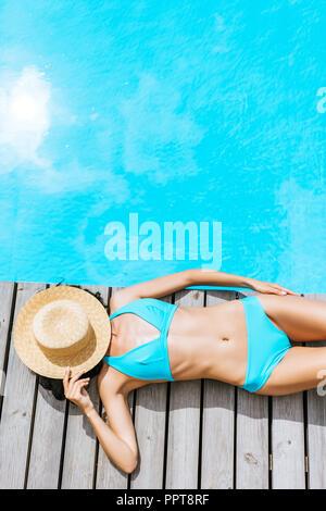 Vue de dessus de young woman in bikini et chapeau de paille sur le visage allongé près de la piscine Banque D'Images