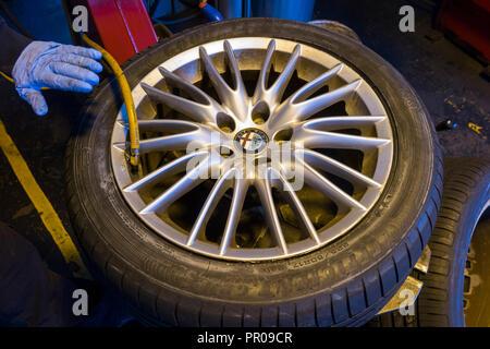 Monteur / mécanicien du gonflage des pneus / gonfle un nouveau pneu nouvellement montée / ( faites par Goodyear ) sur une voiture / Voitures / roue jantes en alliage rim. UK. (102) Banque D'Images