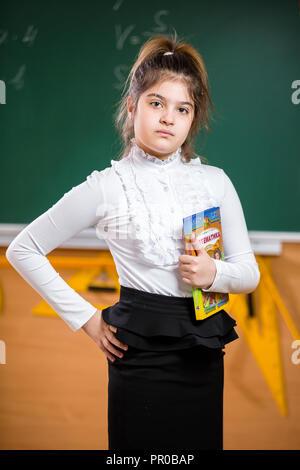 L'Ukraine. Kiev. Le 5 mai 2018. Portrait d'un écolier. Les jeunes de 10 ans Mixed Race girl posing en classe d'école, debout sur un arrière-plan de l'école verte conseil. Thème de l'enseignement collégial Banque D'Images