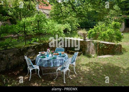 Table et chaises dans la circulaire sur le jardin riverbank Banque D'Images