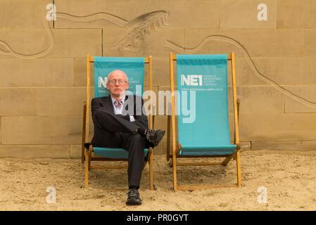 Businessman wearing a suit endormi dans une chaise longue sur la plage par l'homme sur les rives de la rivière Tyne Newcastle Banque D'Images